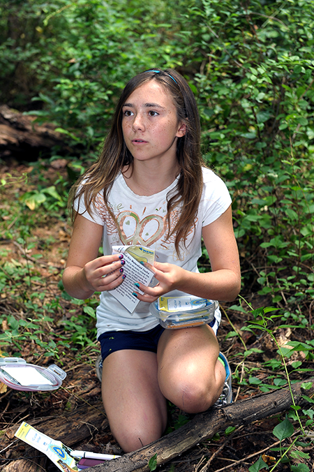 Girl looking through a geocaching box